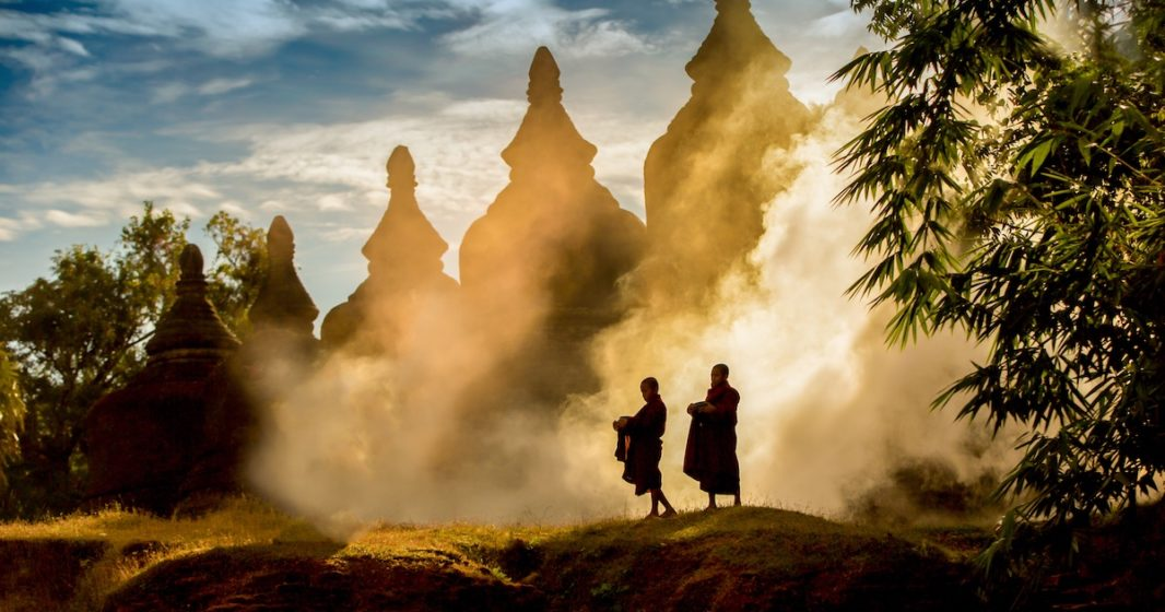 Monks on a mountain with temples in background